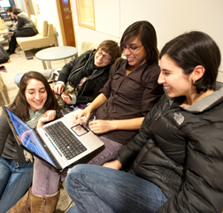 Students smiling looking at laptop in Academic Commons